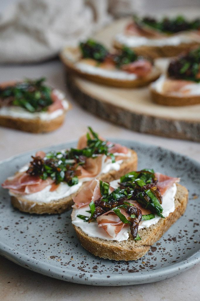 Prosciutto crostini with goat cheese, caramelized onion, and spinach served on a plate