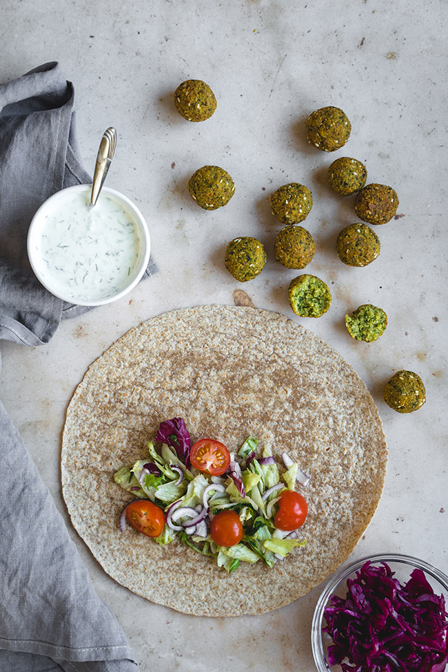 Assembling falafel wrap with vegetables and tzatziki sauce