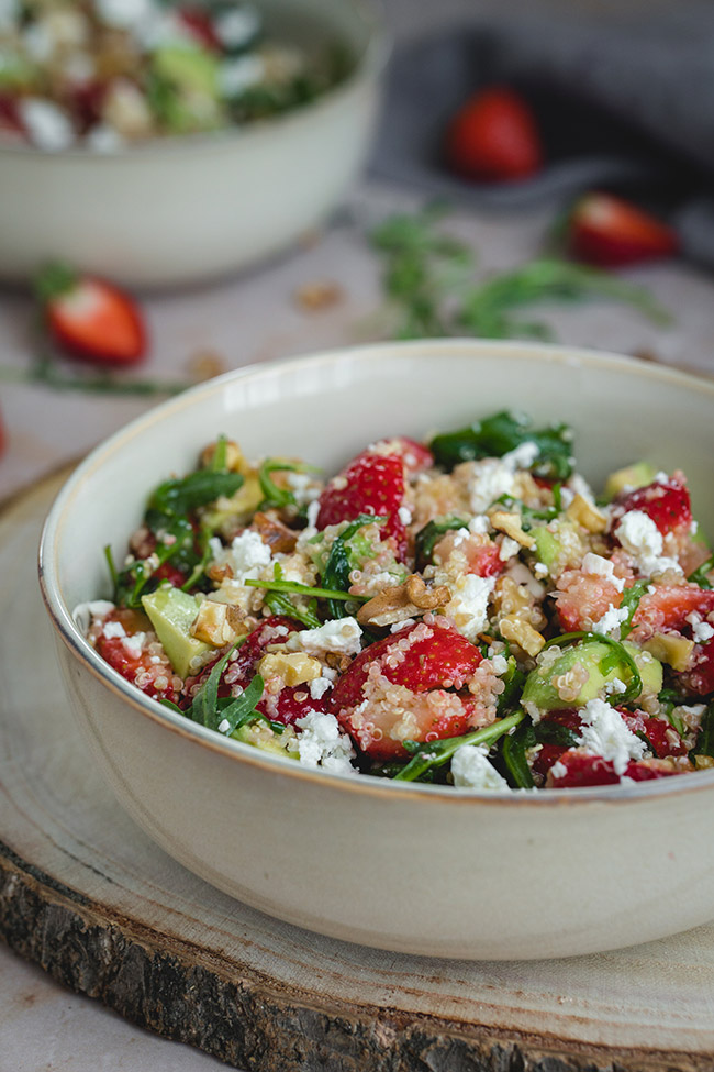 Quinoa Strawberry Avocado Salad with arugula, feta cheese, and walnuts served in a bowl.