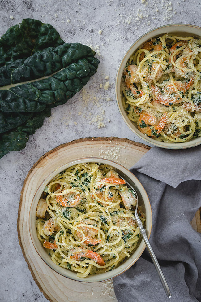 Shrimp kale pasta served in bowls and topped with Parmesan cheese