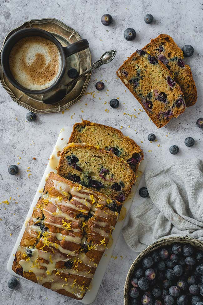 Sliced blueberry zucchini bread served with a cup of coffee