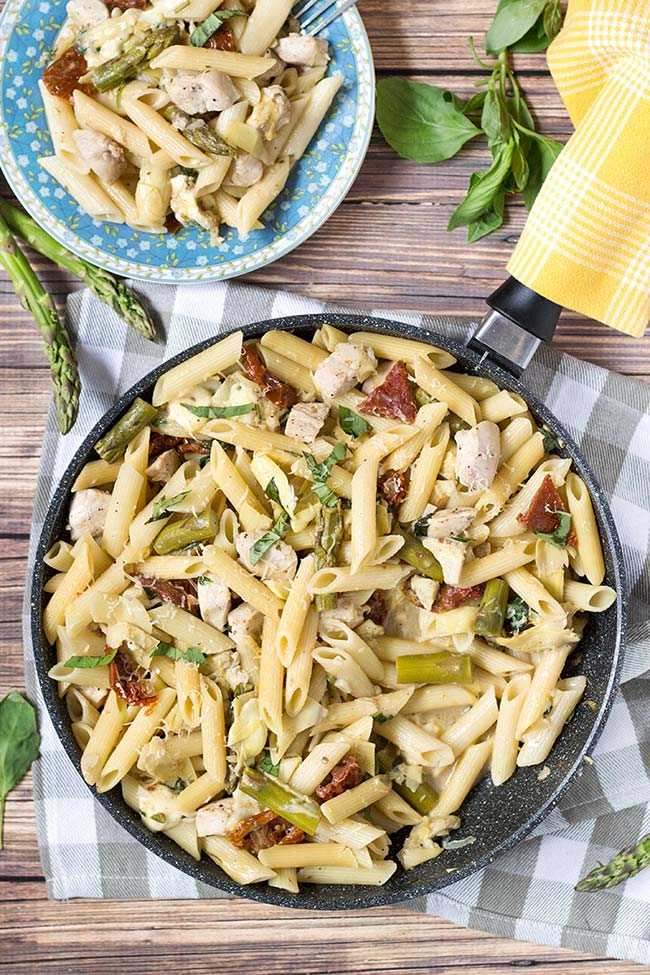 This Chicken Artichoke Pasta also features asparagus and sun-dried tomatoes. It's cheesy and crunchy! l yummyaddiction.com