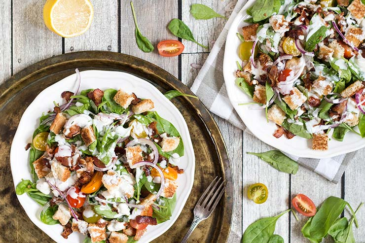 This Spinach Bacon Salad with a buttermilk blue cheese dressing is perfect for a light lunch. It also features tomatoes and croutons that make it even more filling and delicious! | yummyaddiction.com