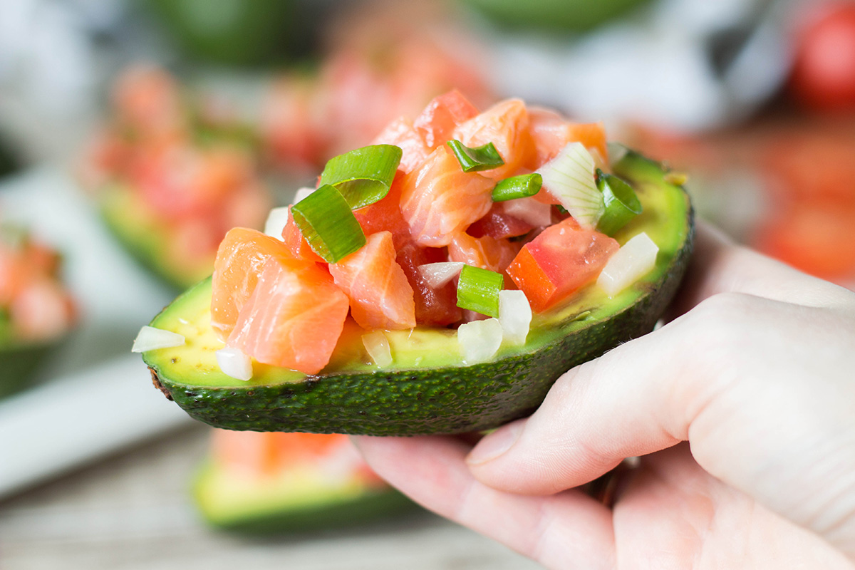 Lomi Lomi Salmon is a famous Hawaiian dish served alongside roasted meats or eaten as a standalone salad. I decided to make an appetizer out of it and served this goodness in avocado halves! | yummyaddiction.com