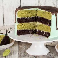 This Green Tea Cake featuring chocolate and matcha cake layers slathered with matcha white chocolate ganache, frosted with vanilla buttercream, and topped with chocolate glaze is a dream! | yummyaddiction.com