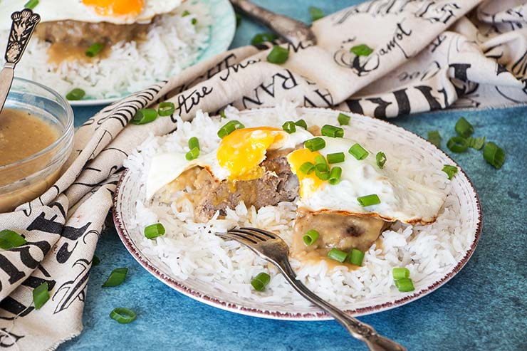 Loco Moco is an iconic Hawaiian dish. A bed of rice is topped with a juicy beef patty, a fried egg, and then drowned in delicious brown gravy! | yummyaddiction.com