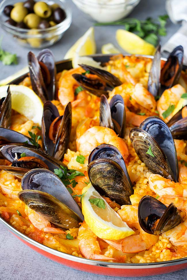 This Spanish Seafood Paella features a crusty saffron and veggie infused layer of rice topped with squid, mussels, and shrimp. The best seafood dish ever!   yummyaddiction.com