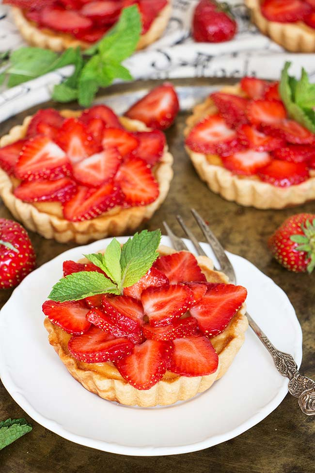 Celebrate summer with these full of flavor Strawberry Custard Tartlets! Lemon-y tart shells filled with creamy custard and topped with fresh strawberries and mint leaves! | yummyaddiction.com