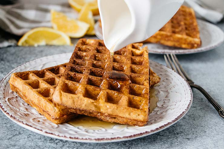Pouring honey over orange poppy seed cottage cheese waffles