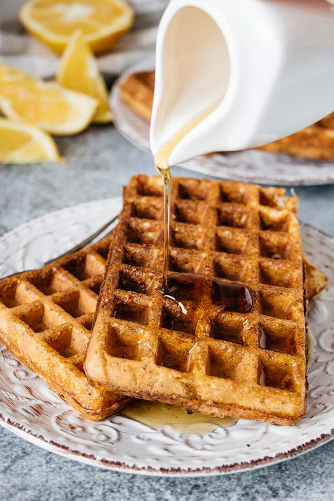 Pouring maple syrup over freshly baked cottage cheese waffles