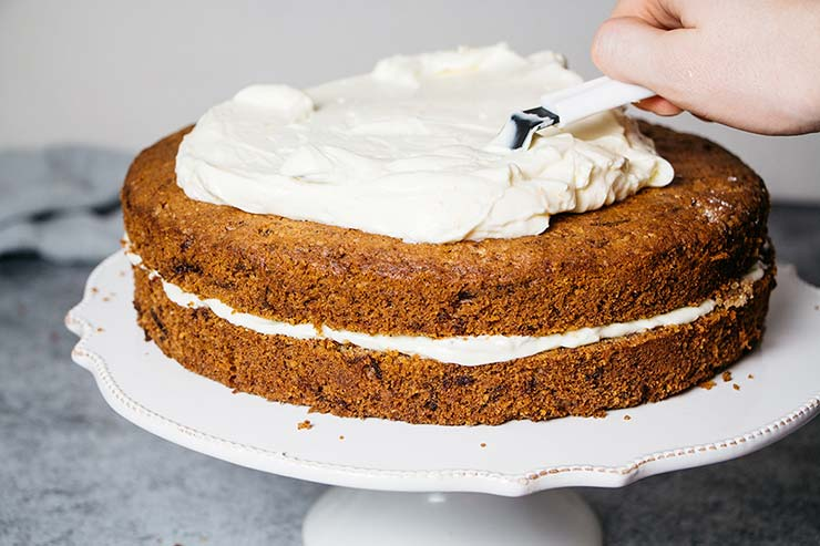 Spreading mascarpone cream cheese frosting on the top of the carrot cake
