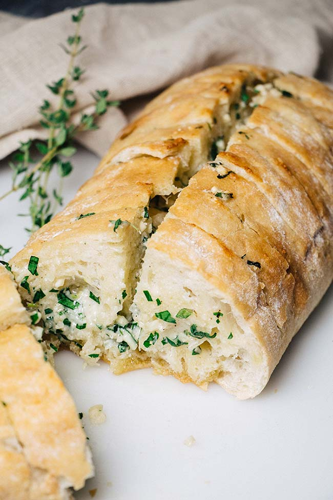 Sliced ciabatta stuffed with butter, garlic, and herb mixture