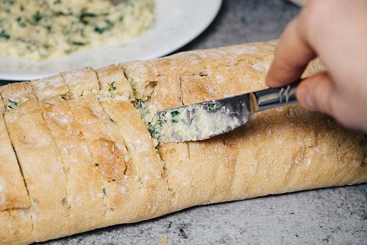 Stuffing ciabatta with garlic, butter, and herb filling