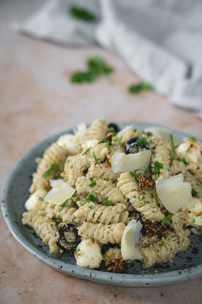 Artichoke pesto pasta served in a plate with Parmesan cheese shavings on top