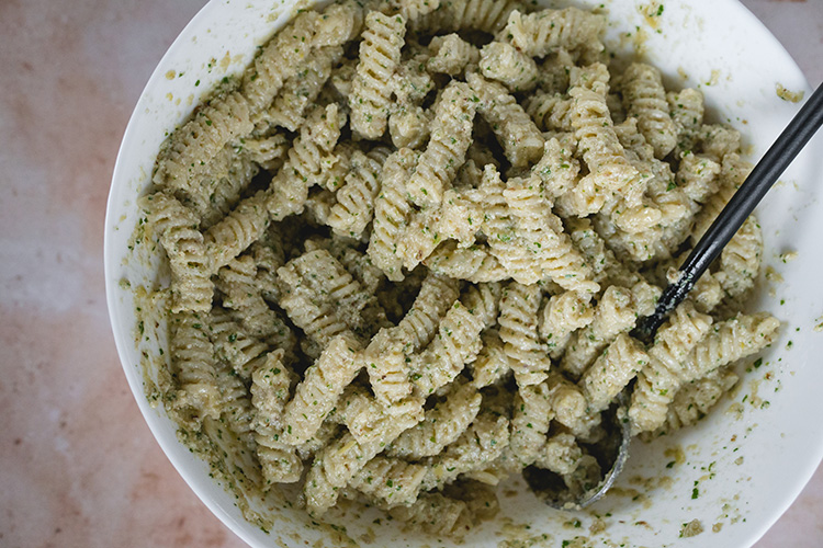 Fusilli tossed with artichoke walnut pesto in a large bowl