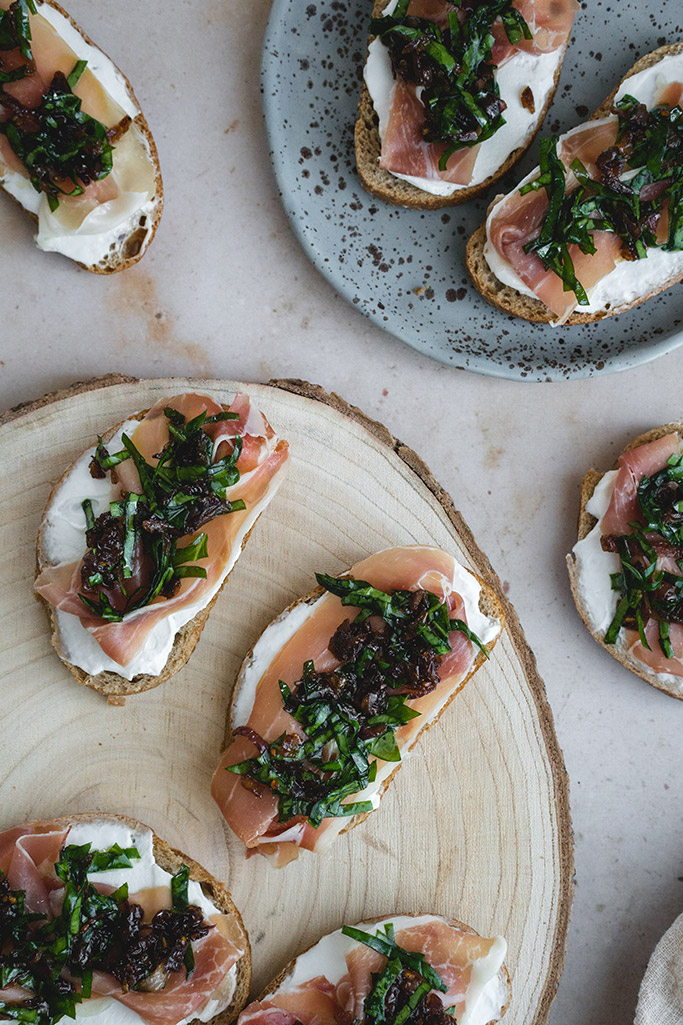 Goat cheese crostini topped with prosciutto and the mixture of caramelized onions and spinach
