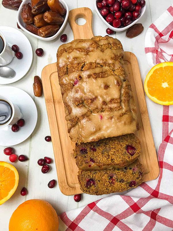 Cranberry orange bread sliced on a cutting board