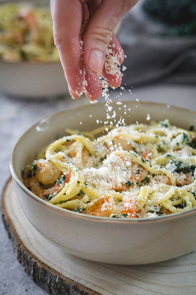Sprinkling parmesan cheese on kale and shrimp pasta