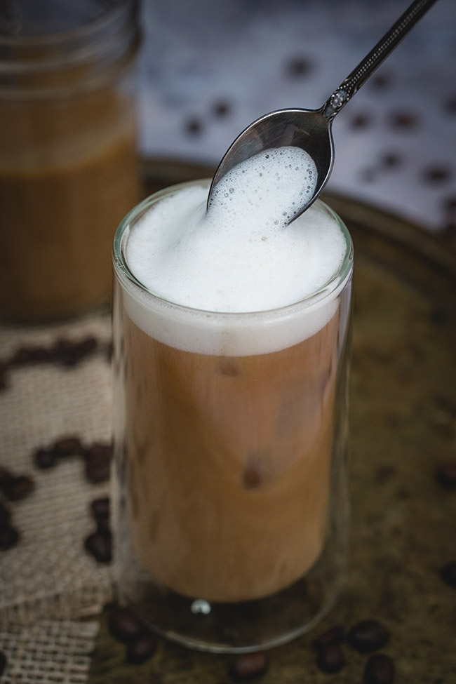 A glass full of foamy iced caramel latte