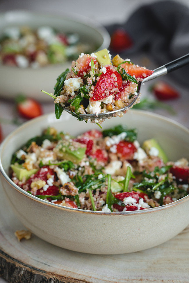A spoonful of summer quinoa salad with strawberries, avocado, feta, arugula, and walnuts