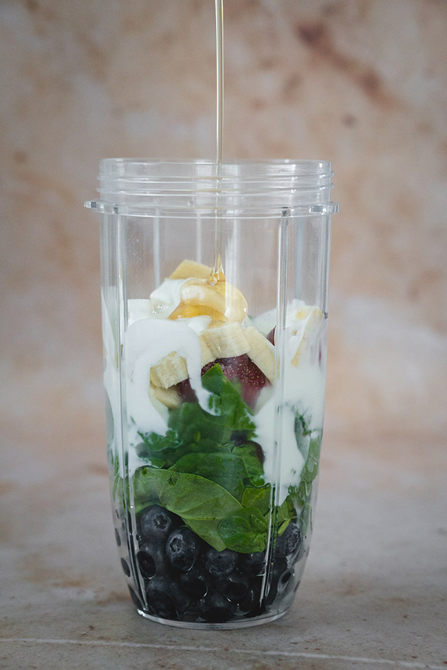 Ingredients for the healthy strawberry blueberry and spinach smoothie in the blender