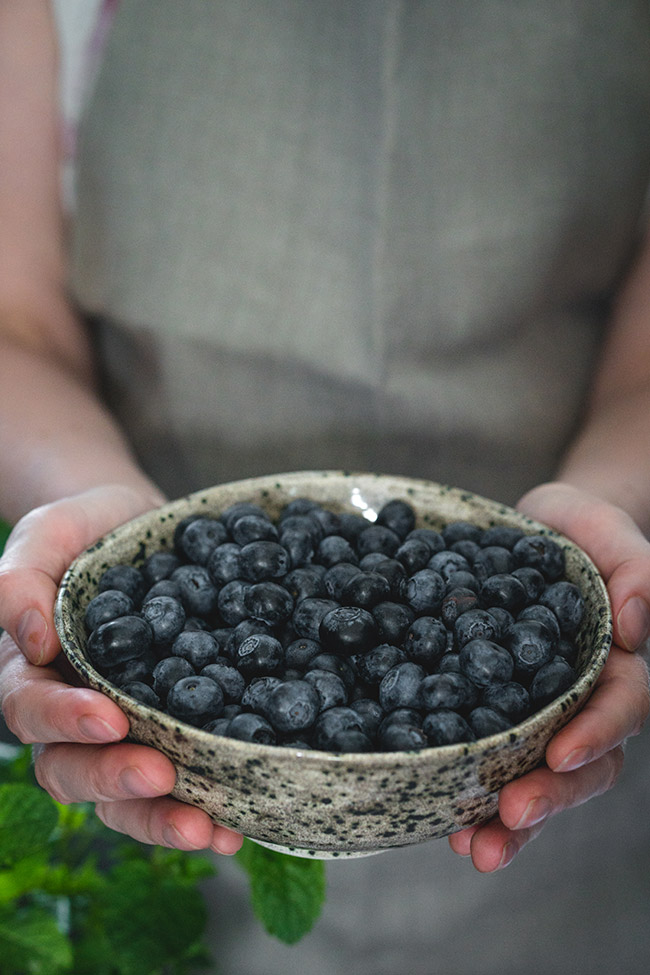 Silver bowl of blueberries held in two hands