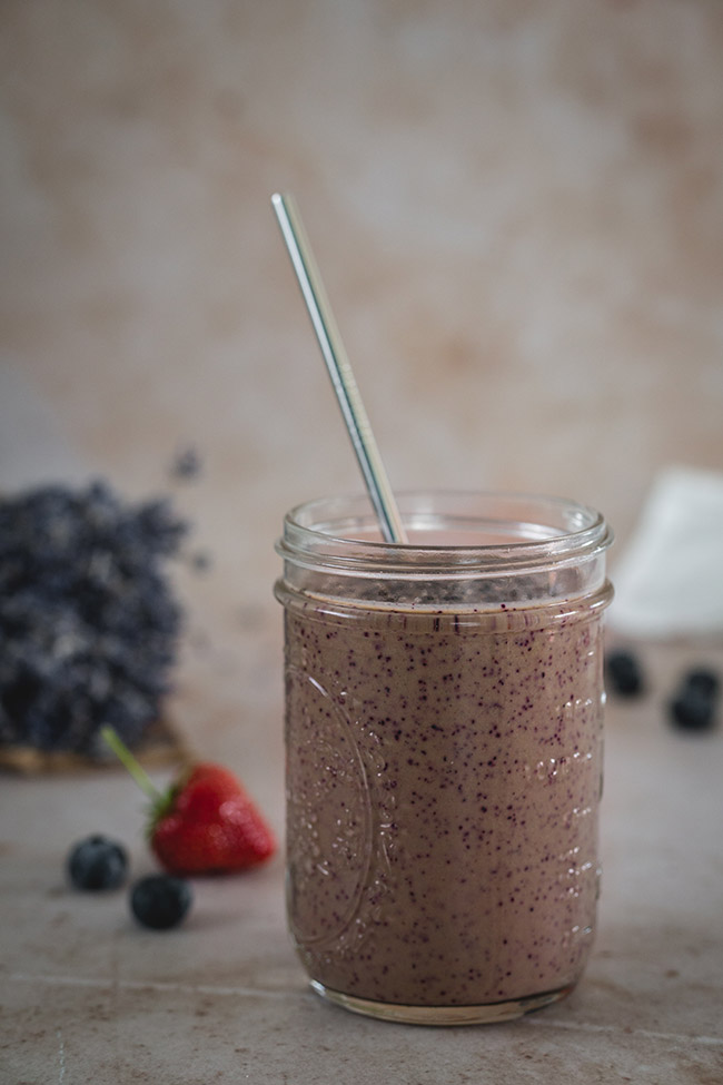 Strawberry blueberry and spinach smoothie in a mason jar with a metal straw