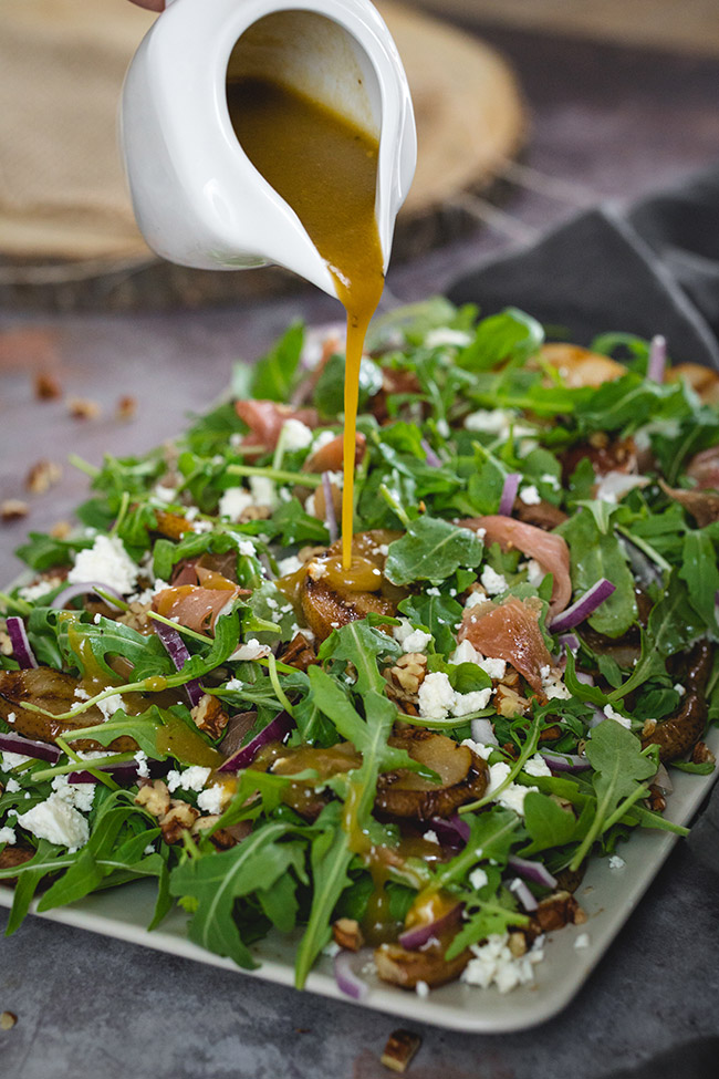 Pouring dressing on the arugula pear salad