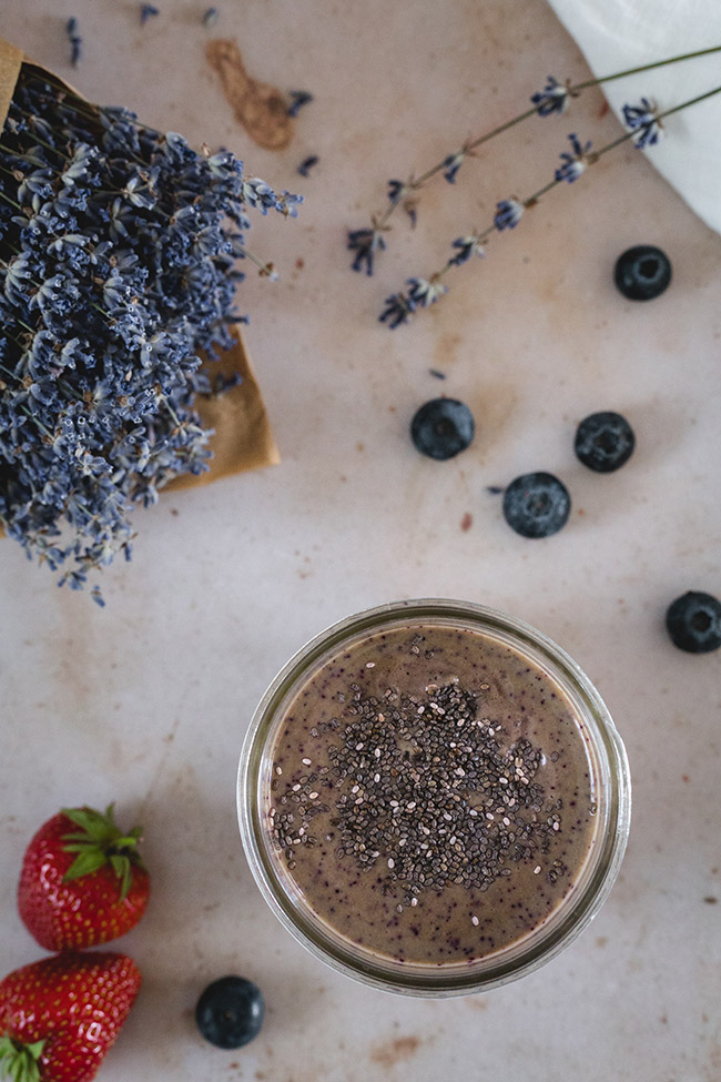 Overhead of smoothie with scattered blueberries and strawberries