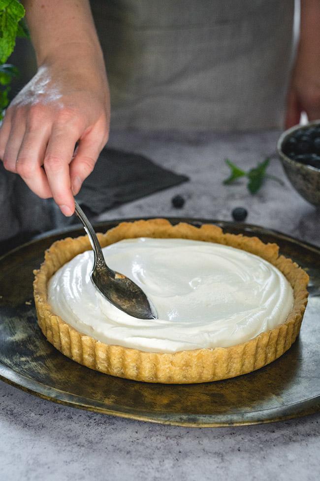 Spooning ricotta filling into spelt tart shell