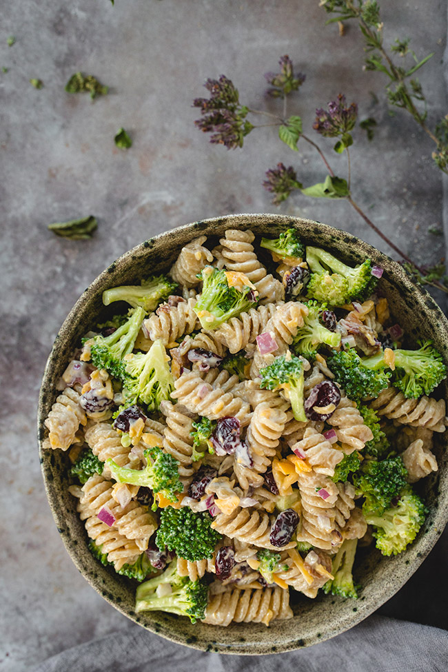A bowl of broccoli pasta salad with cranberries