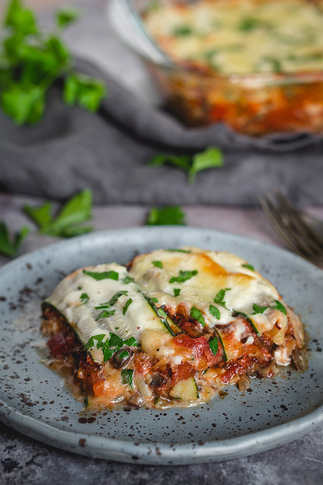 A slice of egetarian zucchini Lasagna with mushroom bolognese on a plate