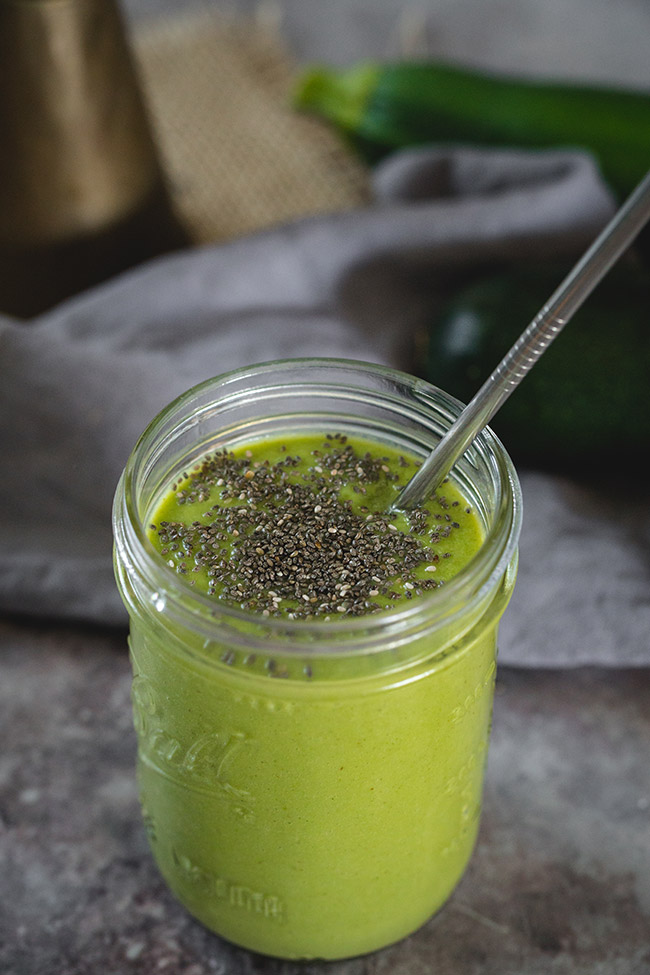 Glass of zucchini, apple and pear smoothie sprinkled with chia seeds