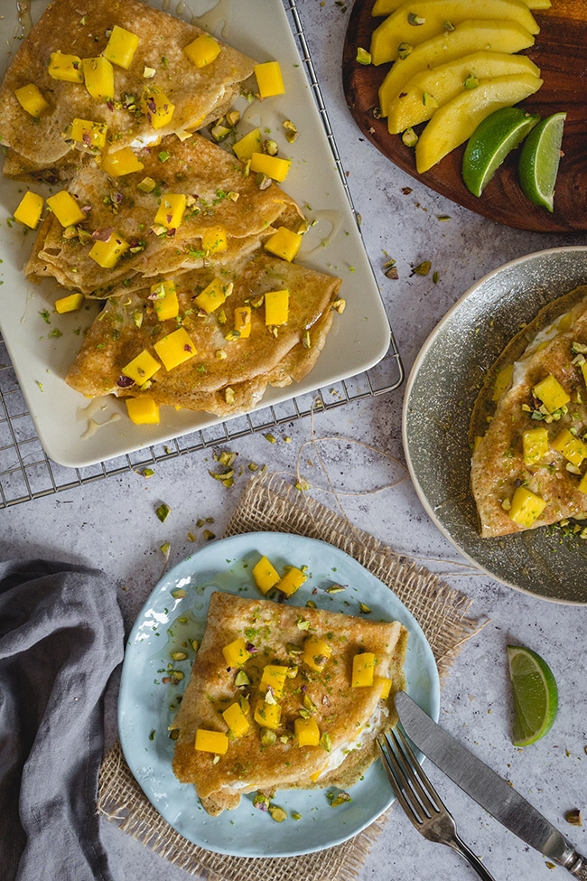 Healthy mango crepes on plates and dishes