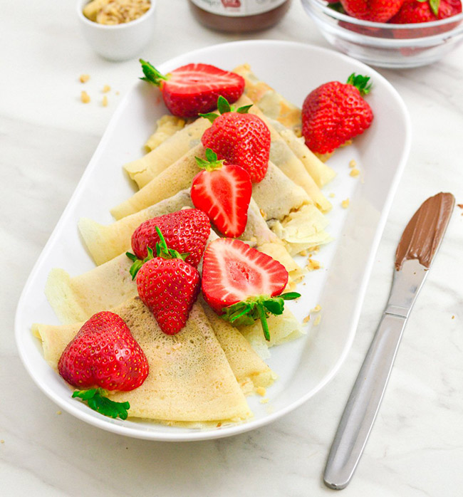 Nutella crepes topped with fresh strawberries