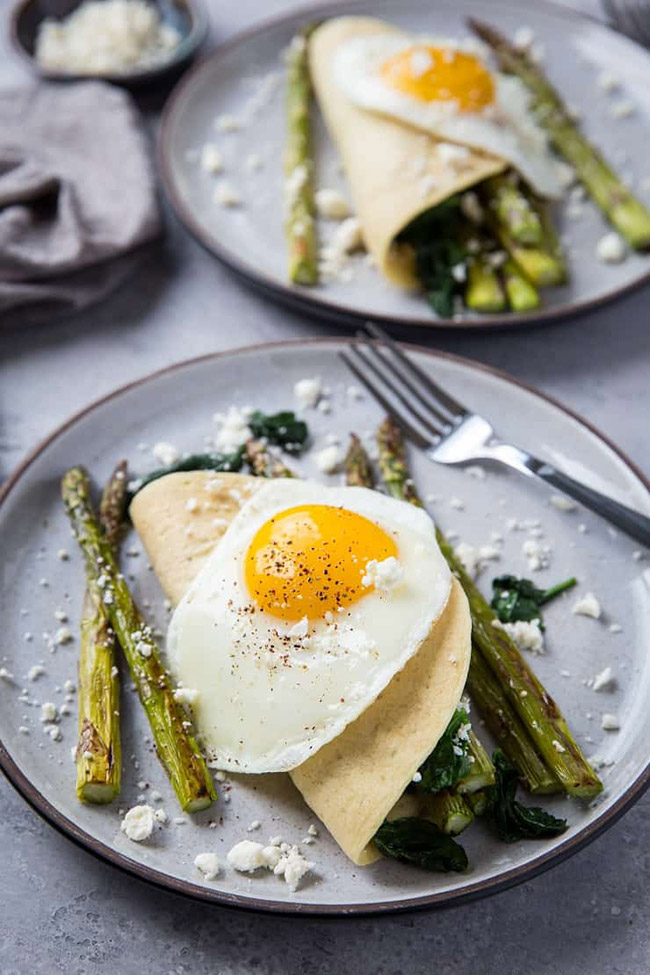 Crepes stuffed with asparagus and topped with a fried egg