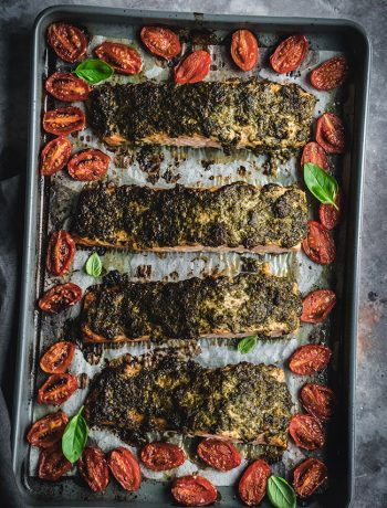 Baked pesto salmon with tomatoes on a tray