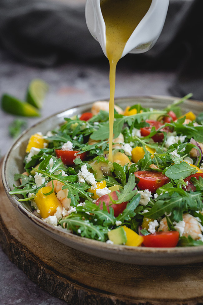 Pouring dressing onto shrimp mango salad