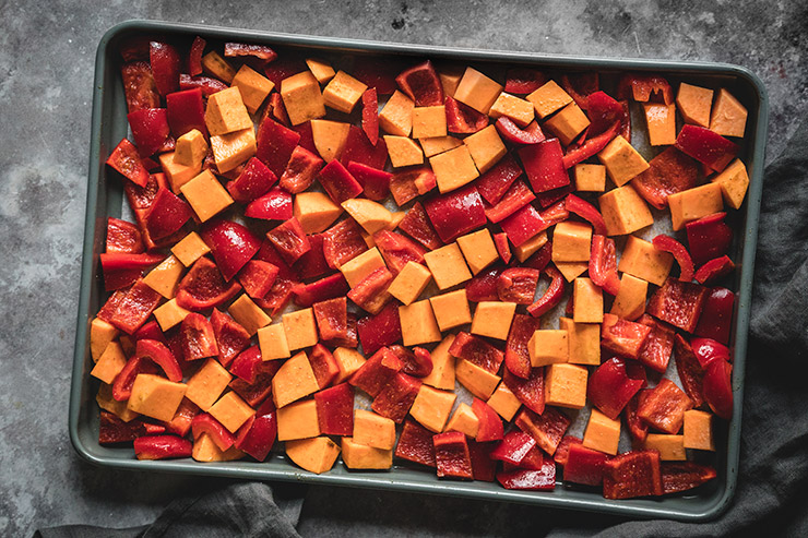 Sweet potatoes and bell peppers on a baking sheet