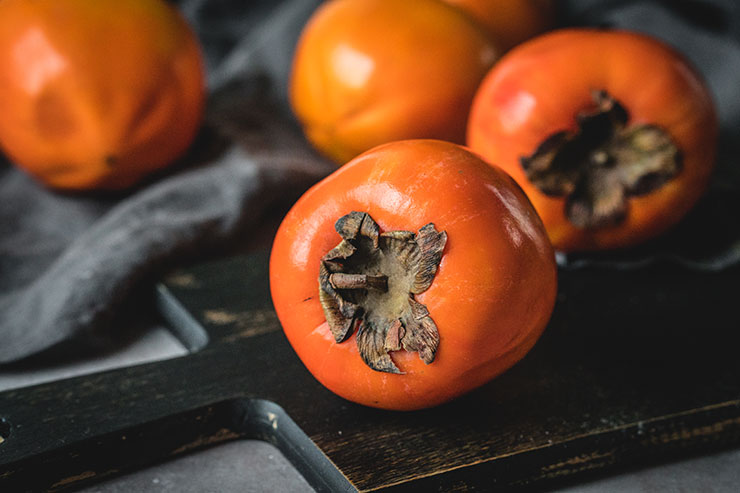 Fresh persimmons on a cutting board