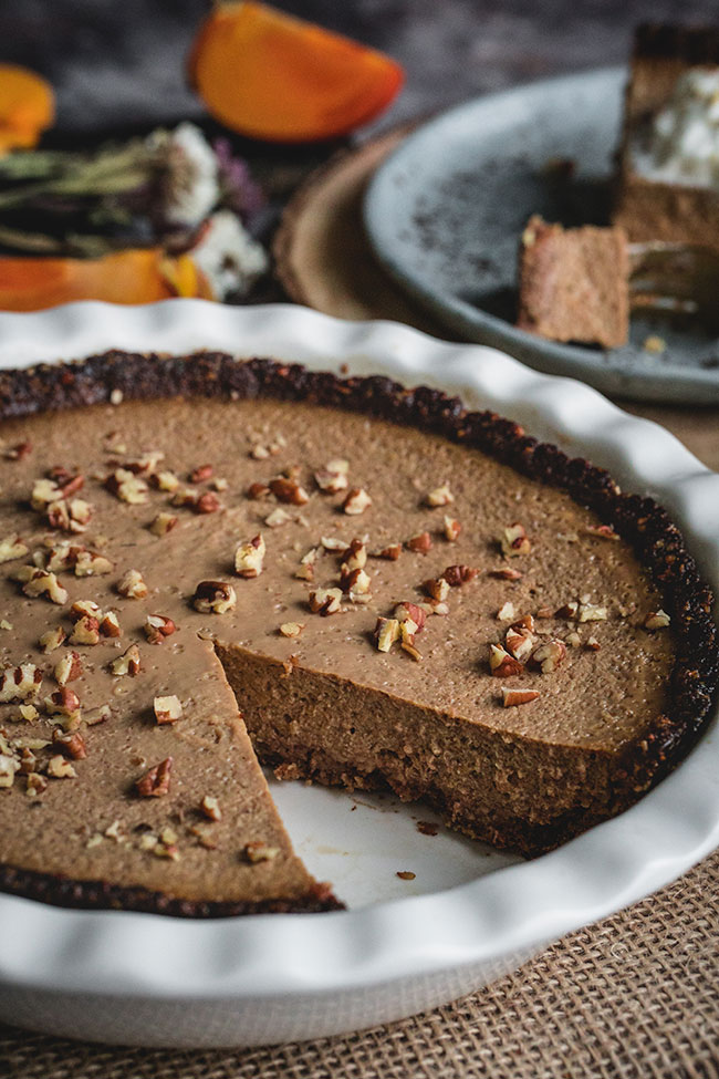 A persimmon pie with an oatmeal, pecan, and date crust topped with chopped pecans
