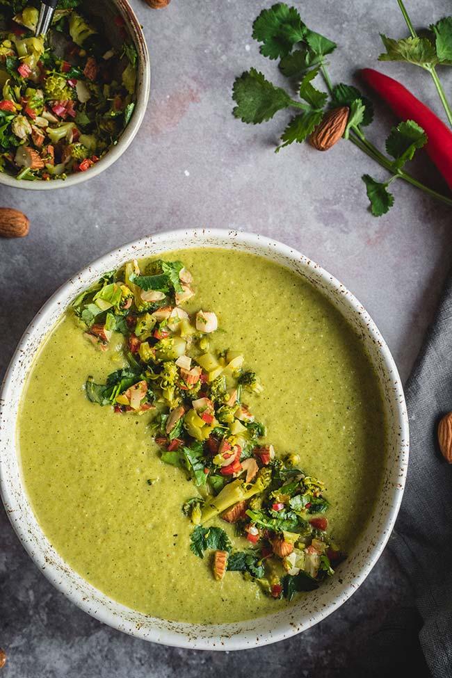 Broccoli almond soup topped with chopped broccoli, cilantro, almonds, and chili pepper