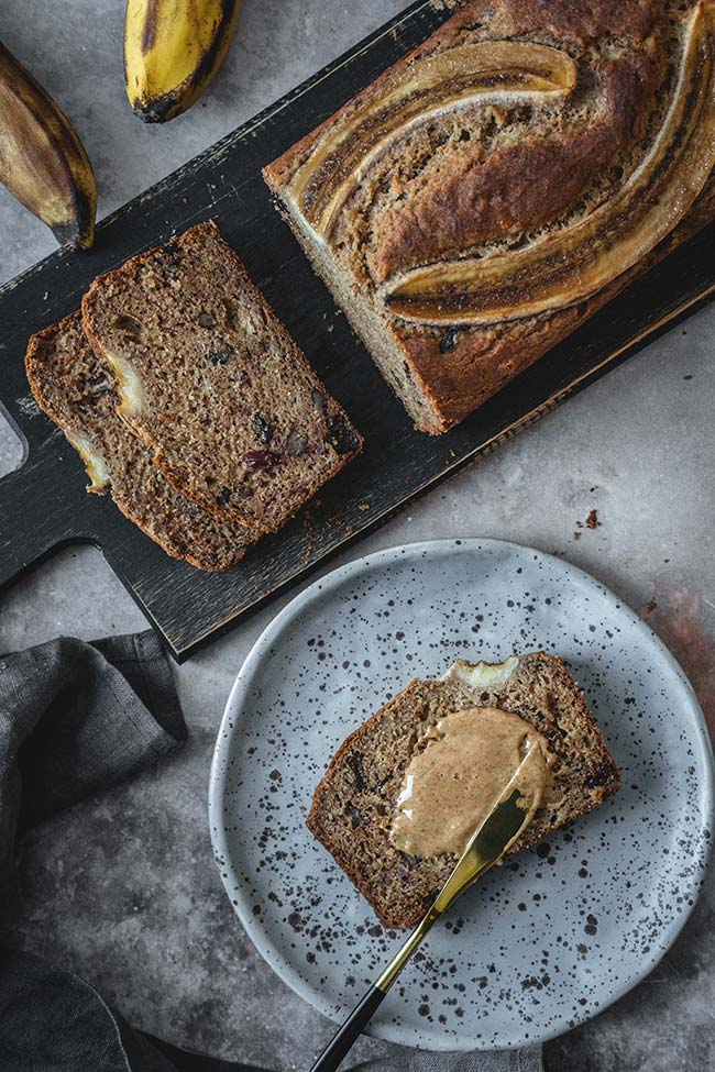 A slice of buckwheat banana bread slathered with peanut butter