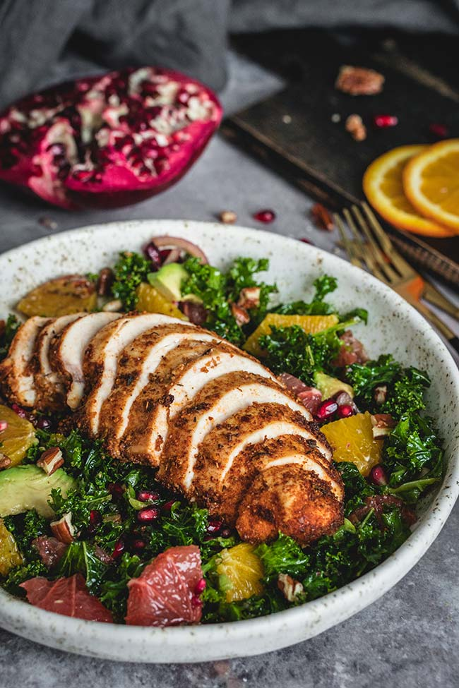Cajun chicken salad with kale, orange, avocado, and pomegranate served on a plate