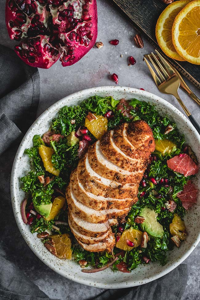 Spiced chicken salad with citrus, kale, and avocado overhead shot