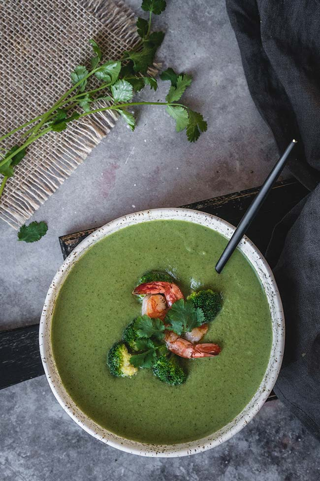 A bowl of broccoli coconut milk soup garnished with shrimp and cilantro