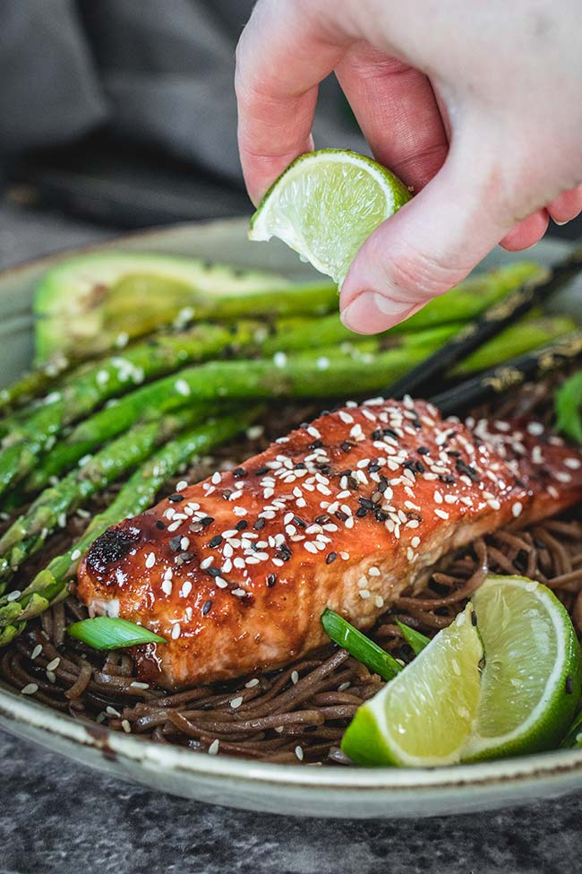 Squeezing lime juice on teriyaki salmon noodles