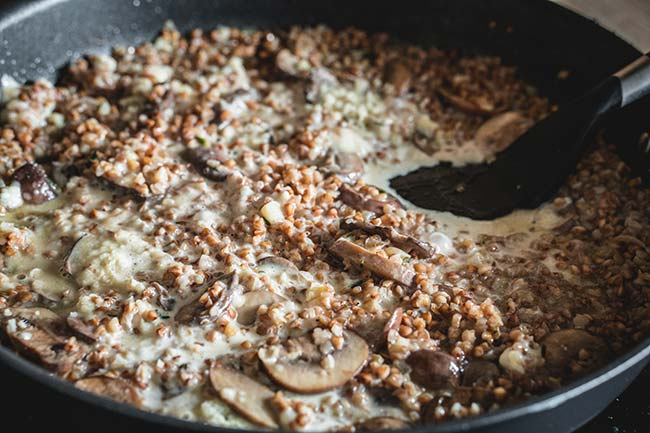 Cooking buckwheat mushroom risotto in a skillet