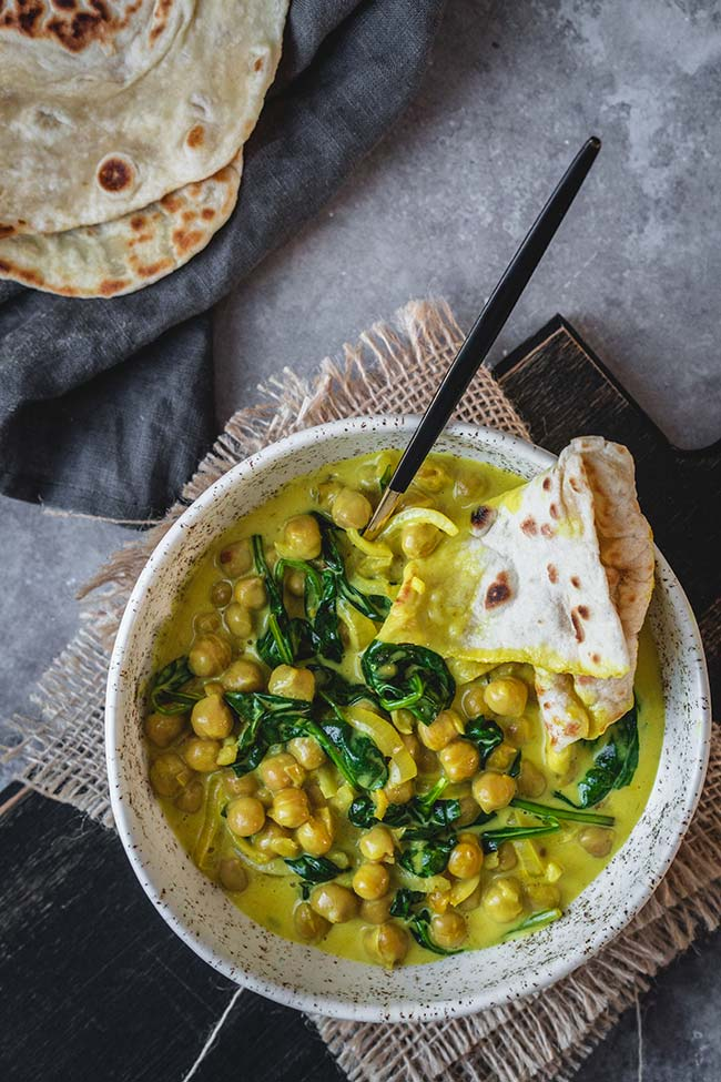 Chickpea curry and Indian flatbread in a bowl.