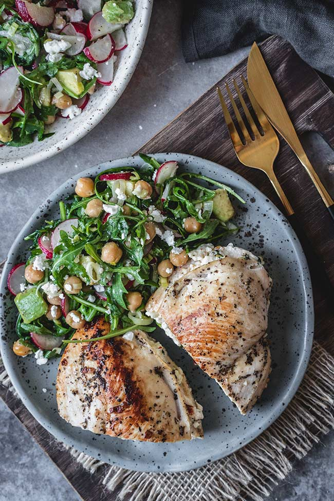Feta and spinach stuffed chicken served with chickpea, avocado, and radish salad